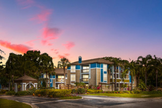 Palm Cove Apartments Entrance at Dusk